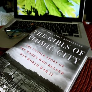 the front cover of The Girl son Atomic City by Denise Kiernan is visible with an open laptop and glasses in the background