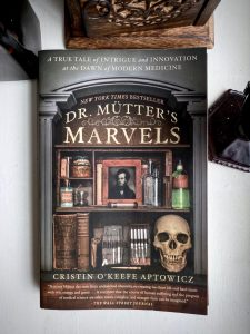 front cover of Dr. Mutter's Marvels by Cristin O'Keefe Aptowicz on a white background. To the left of the book is a bottle with dark liquid, to the top a wooden container engraved with a floral pattern, and to the right the base of deep red goblet.